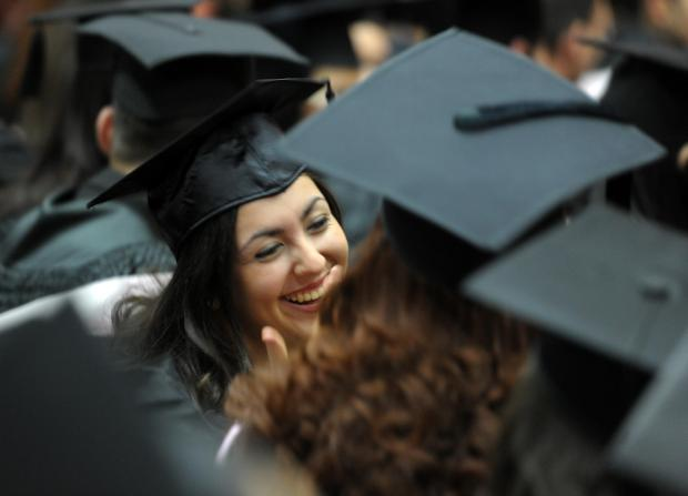 A happy graduate shares her joy with her former classmates on December 2. Photo: Jason Borg