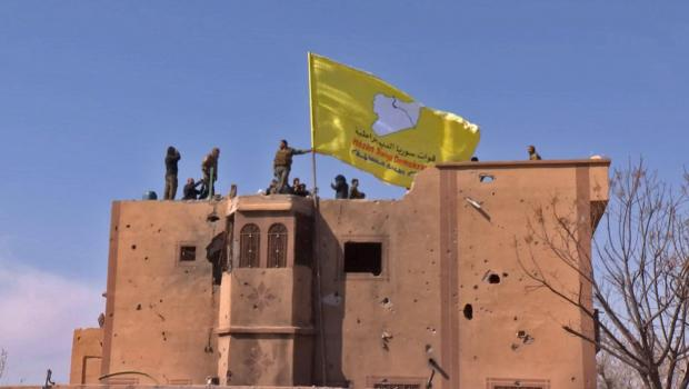 An image grab released by the Kurdish Ronahi TV shows the US-backed Syrian Democratic Forces (SDF) raising their flag atop a building in the Islamic State group's last bastion in the eastern Syrian village of Baghuz.