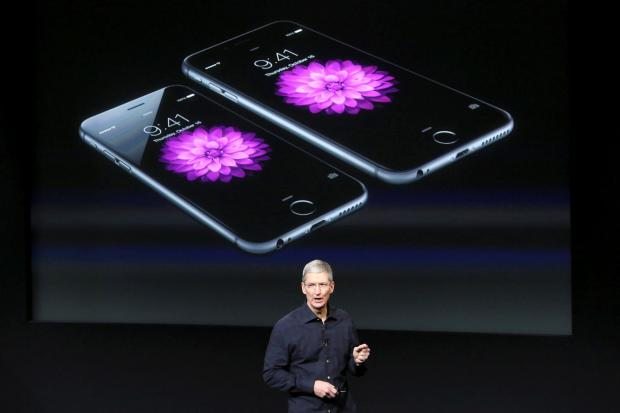 File photo: Apple CEO Tim Cook stands in front of a screen displaying the IPhone 6.