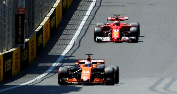 Ferrari's Kimi Raikkonen (back) and McLaren-Honda's Fernando Alonso drive during the third practice session.