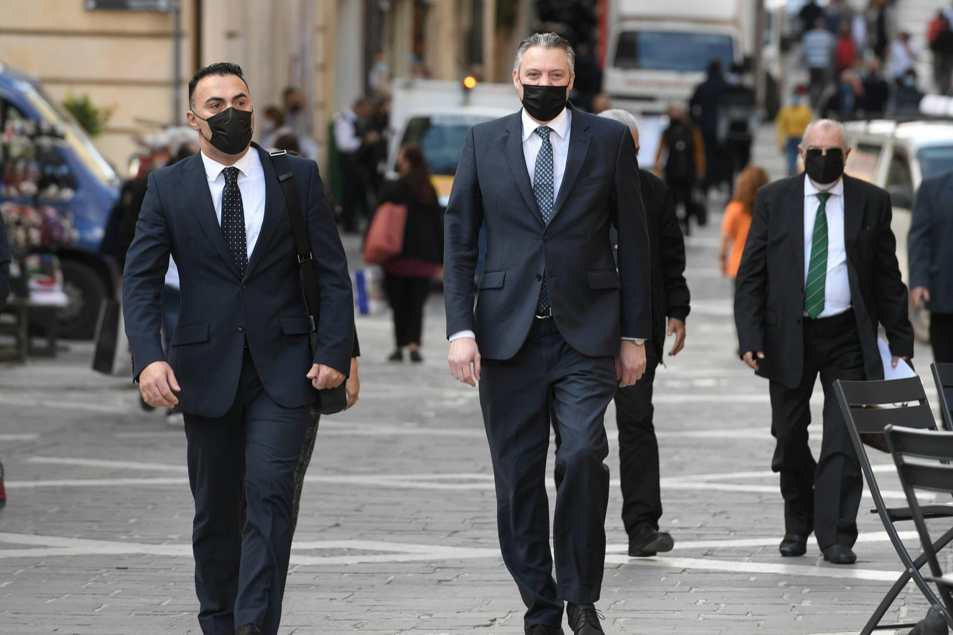Konrad Mizzi (right) walks to court.