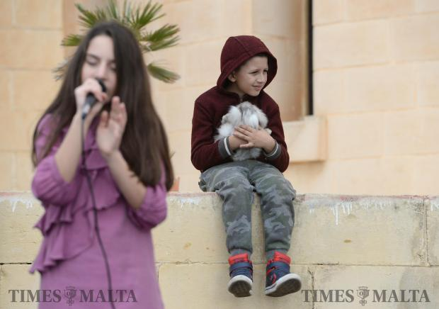 A young boy holds his rabbit as a girl sings on stage at the annual San Martin Festa in Bahrija on November 12. Photo: Matthew Mirabelli