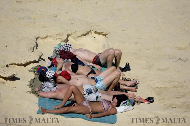 Bathers cover their faces with clothing during a hot summers day in Delimara on September 6. Photo: Mark Zammit Cordina
