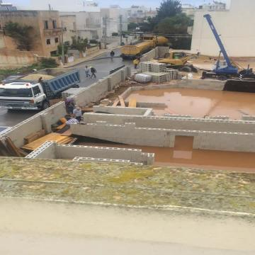 Watch: Flooded roads, stranded motorists and submerged sites as rains lash Malta  | In Naxxar, rains flooded a construction site.