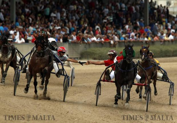 Carmelo Farrugia (red jacket) is congratulated by a fellow driver after leading Quartz De Vindecy to victory in the Premier Class of the French championships at the Marsa Racetrack on June 12. Photo: Darrin Zammit Lupi