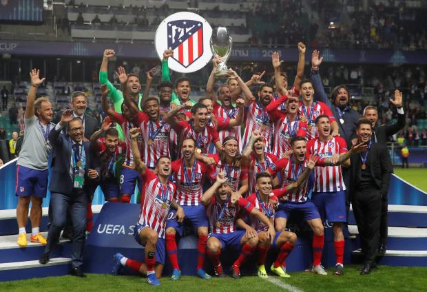 Atletico Madrid celebrate with the trophy after winning the Super Cup.