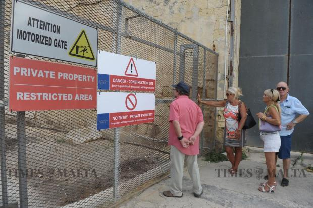 Gzira residents peer through the fence of a gate blocking access to Manoel Island during a protest organized by the Gzira local council on September 5. Photo: Matthew Mirabelli