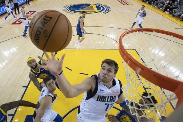 Dallas Mavericks forward Luka Doncic (77) grabs a rebound against the Golden State Warriors during the second half at Oracle Arena. Mandatory Credit: Kyle Terada-USA TODAY Sports