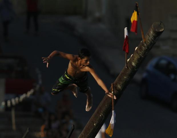 """A child grabs a flag on the """"gostra"""", a pole covered in grease, during the religious feast of St Julian, patron of the town of St Julian's, on August 27. In the traditional """"gostra"""", a game stretching back to the Middle Ages, young men, women and children have to make their way to the top and try to uproot one of the flags to win prizes. Photo: Darrin Zammit Lupi"""