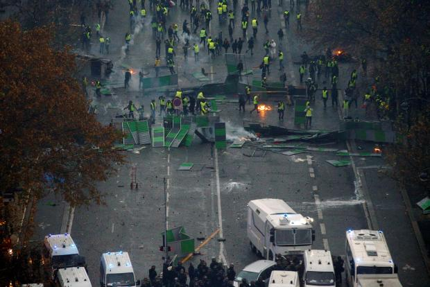 Police barricades on one side, yellow vest protesters on the other near the Place de l'Etoile in Paris. Photo: Reuters
