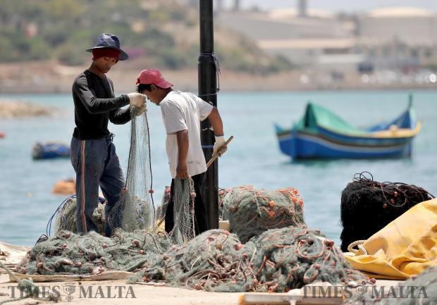 Fishermen fix their nets in Marsaxlokk on June 1. Photo: Chris Sant Fournier