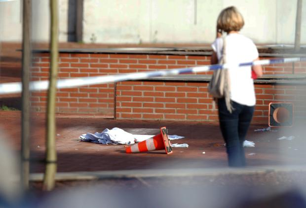 A woman stands at the site where a machete-wielding man injured two female police officers before being shot outside the main police station in Charleroi.