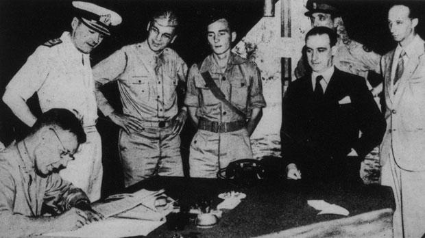 General Walter Bedell Smith signing, on behalf of the Allies, the Italian armistice at Cassibile, Sicily, as various US, British and Italian officials look on.