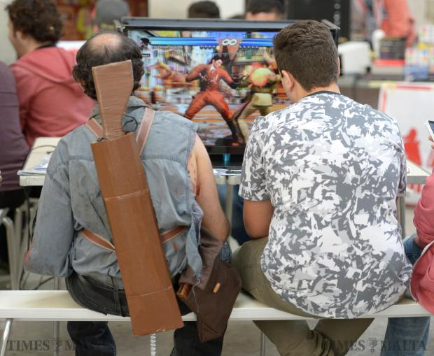 Two enthusiasts, one of them with a mock-up shotgun strapped to his back, follow a video game at the seventh edition of the Malta Comic Con held over the weekend of December 5 and 6 at Valletta Waterfront. Photo: Matthew Mirabelli