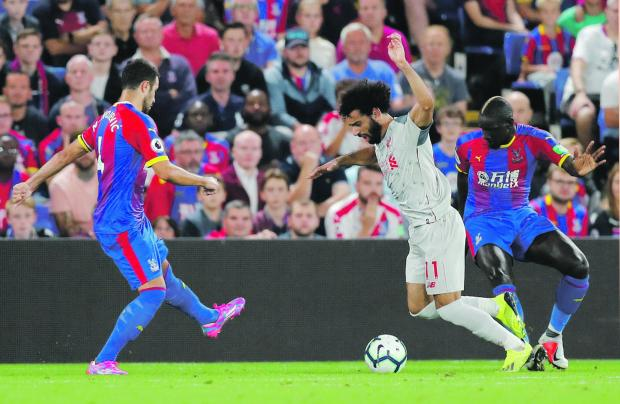 Liverpool's Mohammed Salah (no. 11) is brought down inside the area by Mamadou Sakho.