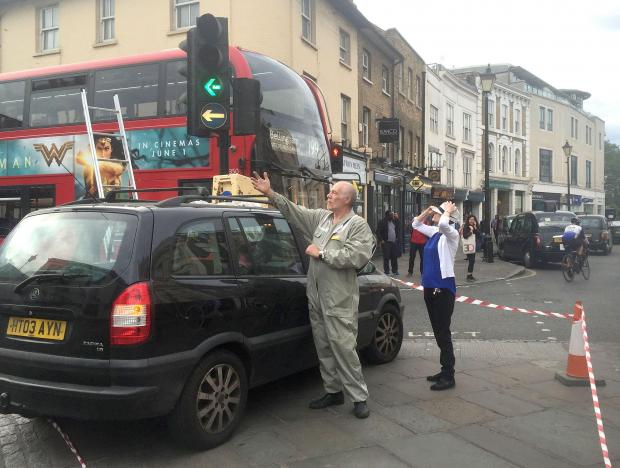 Beekeeper Phil Clarkson uses a portable hive placed on the roof of a vehicle to capture a swarm of bees at Greenwich Church Street yesterday evening.