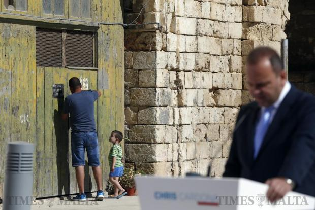 A man and child leave a warehouse at Dock One as Labour Party MP Chris Cardona launches his deputy leadership electoral campaign in Cospicua on May 21. Photo: Darrin Zammit Lupi