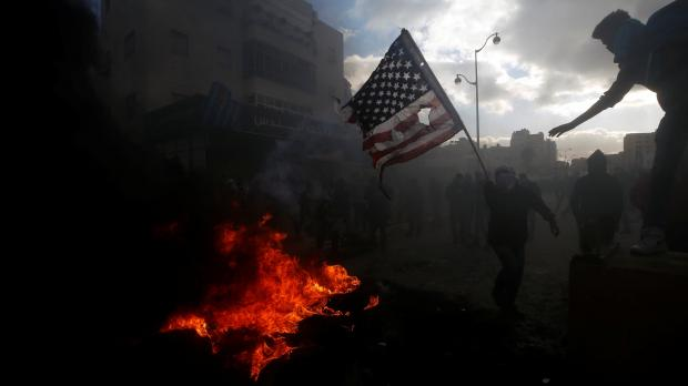 A Palestinian protester prepares to burn a US flag during clashes with Israeli troops at a protest against President Trump's decision to recognise Jerusalem as the capital of Israel. Photo: Reuters
