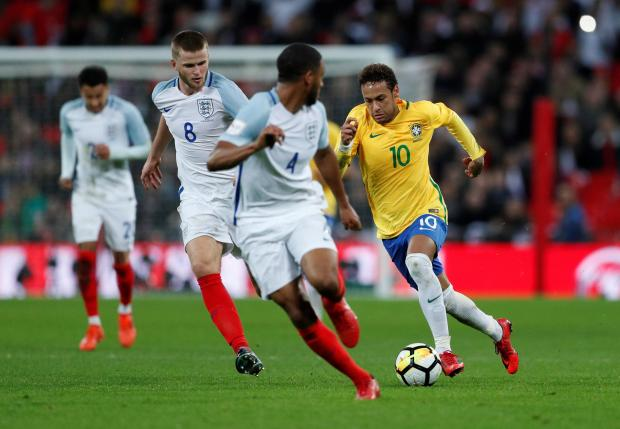 Brazil's Neymar in action with England's Eric Dier and Joe Gomez.