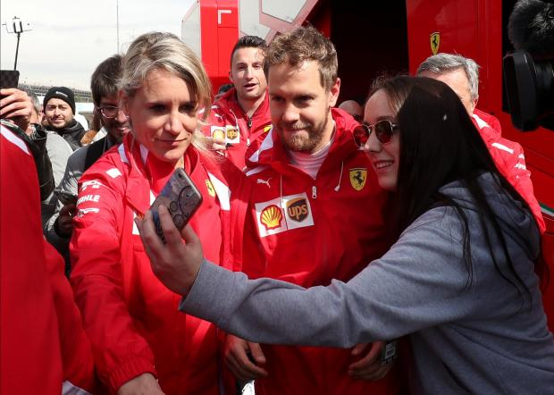 Sebastian Vettel poses for a selfie with a Ferrari fan in Barcelona.
