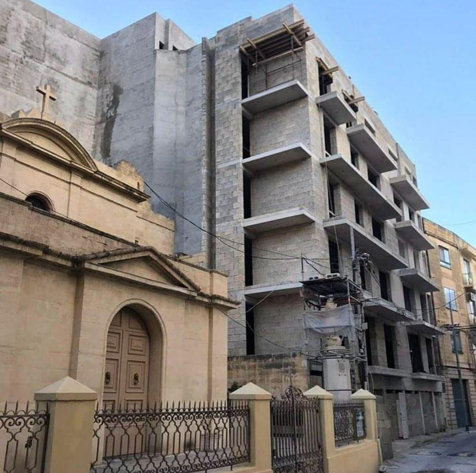 A development in Msida which towers over a chapel next door.