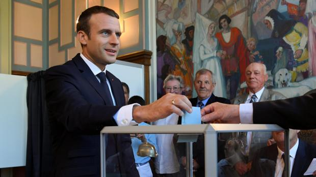 Macron casts his vote in parliamentary elections. Photo: Reuters