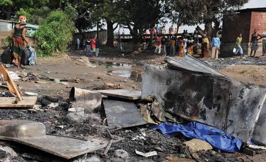 Residents of the Abidjan looking at the covered charred body of a soldier. Photo: Issouf Sanogo/AFP