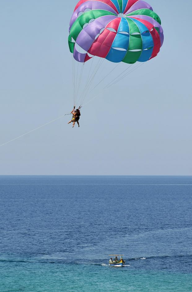 A couple dangle from a parachute towed by a boat in Golden Bay on July 11. Photo: Chris Sant Fournier