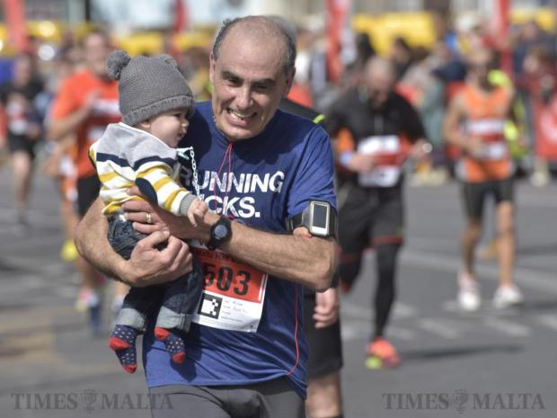A participant carries a child as he approaches the finishing line of the Malta Marathon in Sliema on 28 February. Photo: Mark Zammit Cordina