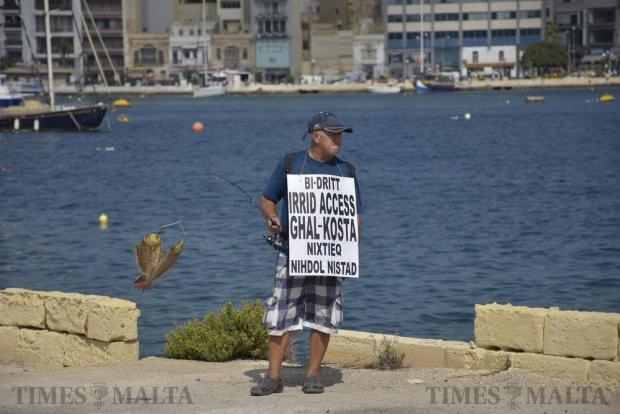"A protestor carrying a placard reading ""Our right to access the foreshore – I want to go in and fish"" takes part in a protest on Manoel Island on September 24. Photo: Mark Zammit Cordina"