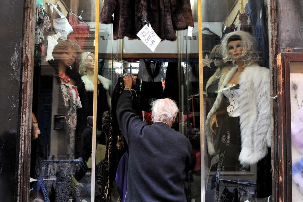 A shopkeeper removes items of clothing from the front of his shop in Valletta on January 3. Photo: Chris Sant Fournier