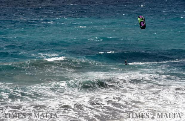 A kite surfer cuts through the large waves in Golden Bay as strong winds hit the island over the past few days. Photo: Matthew Mirabelli