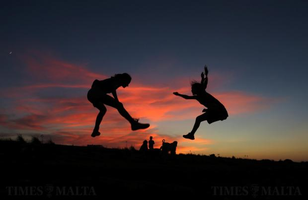 Two girls practice their gymnastics straddle jumps while taking a break from walking a dog in Pembroke, at sunset on August 6. Photo: Darrin Zammit Lupi