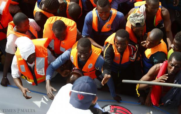 Migrants reach out to climb aboard the NGO Migrant Offshore Aid Station (Moas) ship Phoenix as a group of 106 sub-Saharan Africans on board a rubber dinghy is rescued off the Libyan coast on October 4. Photo: Darrin Zammit Lupi/Moas