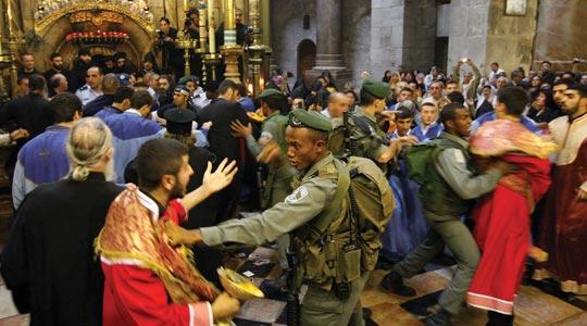 An Israeli police officer holds back a member of the Armenian clergy (left) in the church of the Holy Sepulchre in Jerusalem's Old City, yesterday.