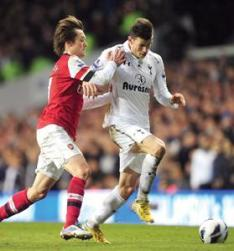 Tottenham's Gareth Bale (right) is challenged from behind by Tomas Rosicky, of Arsenal.