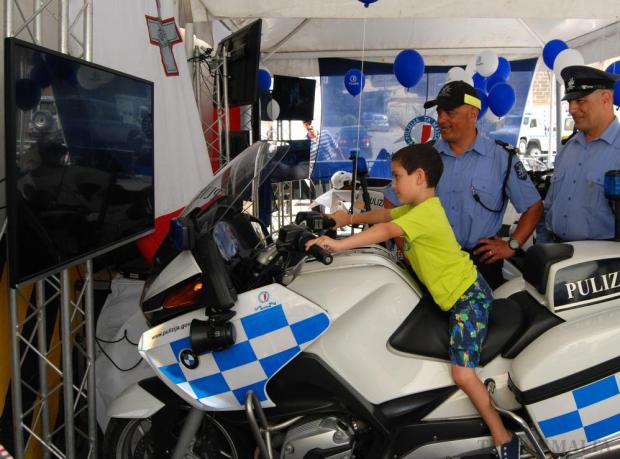 Two traffic policemen show a boy a simulation of riding a police motorcycle during the police day activities held at Notre Dame Ditch in Floriana on July 4. Photo: Mark Zammit Cordina