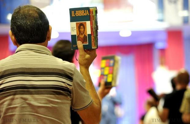 A member of the River of Love Evangelical Movement raises his Bible during a sermon by Texan Bishop Tom Brown on June 12. Photo: Chris Sant Fournier