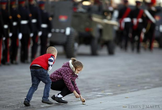 Children rush onto the parade ground to collect spent rifle cartridges after an Armed Forces of Malta military parade to mark Malta's Republic Day in Valletta on December 13. Malta, a former British colony, became a republic in 1974, 10 years after gaining independence. Photo: Darrin Zammit Lupi