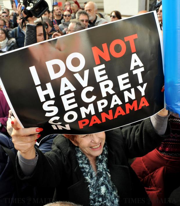 A woman holds up a plackard at the Demonstration against corruption organised by the Nationalist Party in Valletta on February 19. Photo: Chris Sant Fournier