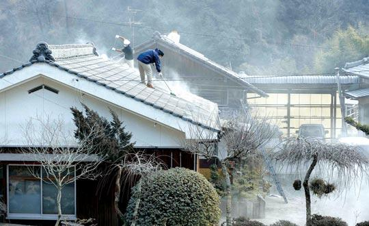 Residents clearing volcanic ash released by the erupting Shinmoedake volcano from the roof of their house in Miyakonojo, Miyazaki prefecture, yesterday. Shinmoedake, the 1,421-metre-high volcano on the border of Miyazaki and Kagoshima prefectures in southwestern Japan, was still active after its first major eruption in 52 years in late January. Photos: Kazuhiro Nogi/AFP