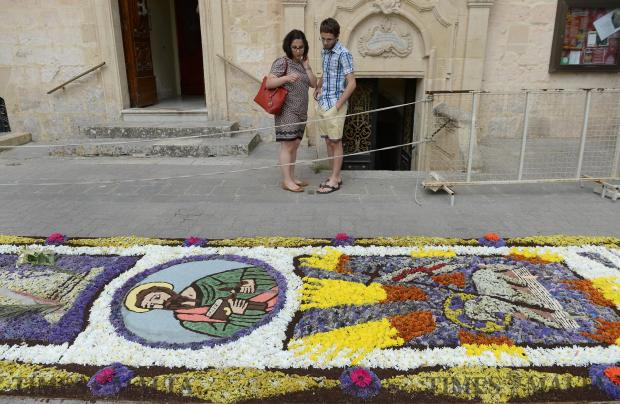A couple admire the Infiorata display outside St Paul's Church in Rabat on June 18. Photo: Matthew Mirabelli