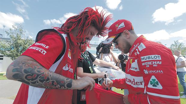 Sebastian Vettel (right) signs an autograph to a Ferrari fan in Melbourne, yesterday.
