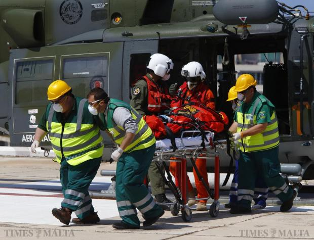 Paramedics wheel an ill migrant on a stretcher away from an Italian military AB212 II helicopter after it landed at St Luke's Hospital in Gwardamangia on April 13. The female migrant, believed to be Somali, was rescued by a merchant vessel and flown to Malta as part of the ongoing search and rescue operations taking place in the southern Mediterranean. Photo: Darrin Zammit Lupi