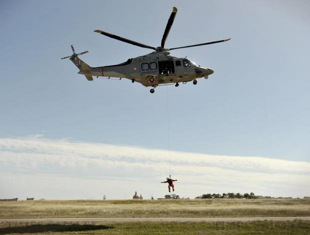 A rescuer dangles from an Armed Forces of Malta AgustaWestland AW139 helicopter during an exercise at Malta International Airport on March 6. Photo: Chris Sant Fournier