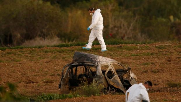 Forensics experts near the remains of Caruana Galizia's car late yesterday - Photo Reuters/Darrin Zammit Lupi.