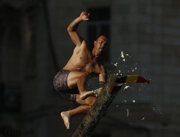 "A man slips off the ""gostra"", a pole covered in grease, during the religious feast of St Julian, patron of the town of St Julian's, on August 28. In the traditional ""gostra"", a game stretching back to the Middle Ages, young men, women and children have to make their way to the top and try to uproot one of the flags to win prizes. Photo: Darrin Zammit Lupi"