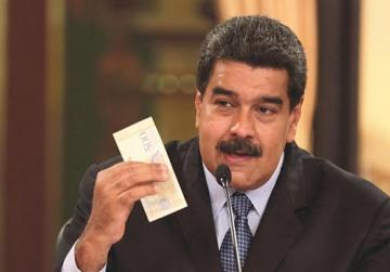 Venezuela's President Nicolás Maduro holds a bank note from the new Venezuelan currency bolivar soberano as he speaks during a meeting with ministers in Caracas. Photo: Reuters