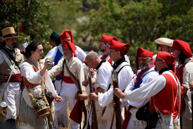 A woman sprays sunblock on to re-enactors before a battle in San Maison on June 5. Photo: Mark Zammit Cordina