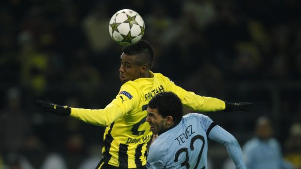 Borussia Dortmund's Felipe Santana and Manchester City's Carlos Tevez (R) jump for the ball.